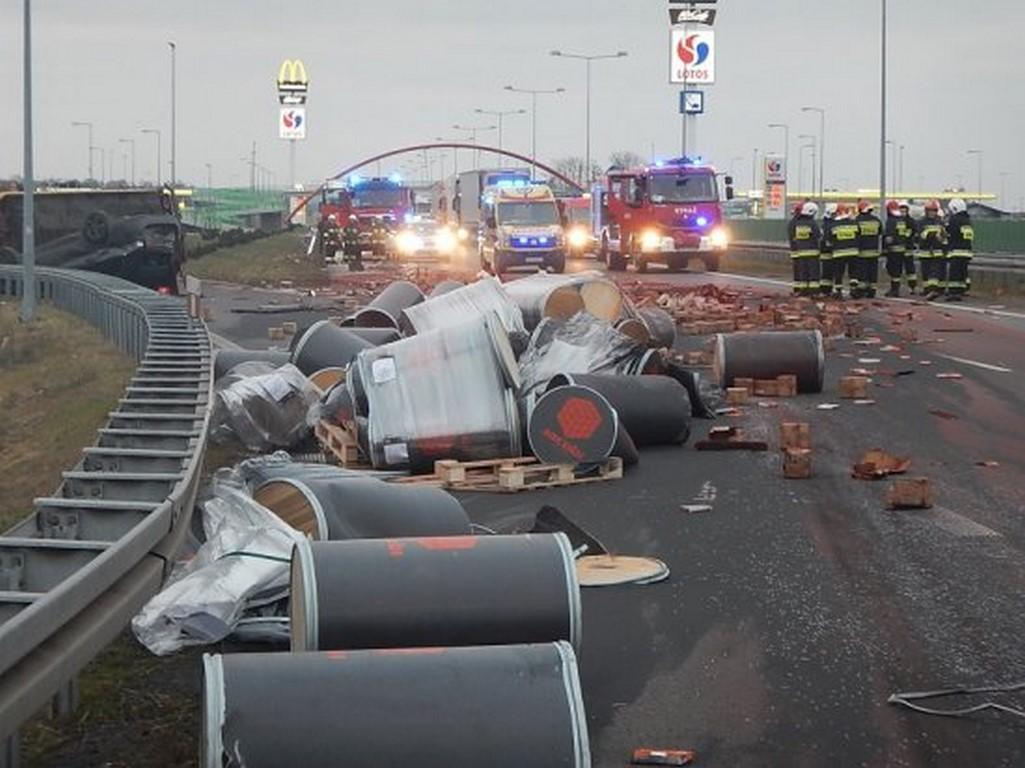 Bardzo niebezpieczny wypadek na autostradzie A 2. Zderzenie ciężarówki DAF zsamochodem marki IVECO, który przewoził auto osobowe. Na jezdni beczki z surowcami budowlanymi